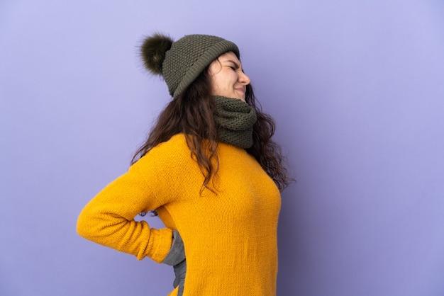 努力をしたために腰痛に苦しんで紫色の壁に隔離された冬の帽子を持つ10代のロシアの女の子