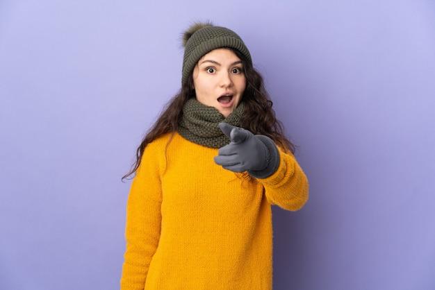 紫色の壁に分離された冬の帽子を持つティーンエイジャーのロシアの女の子は驚いて正面を指しています