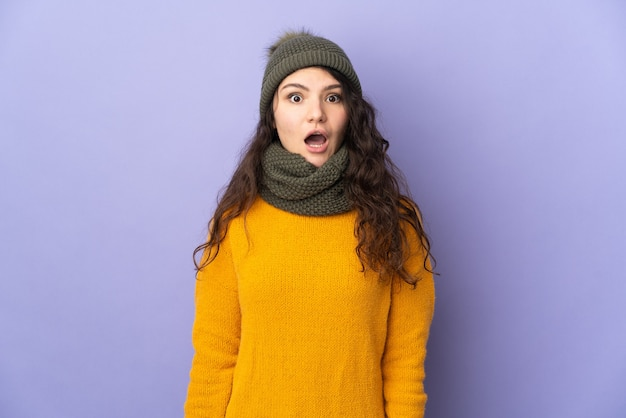 驚きの表情で紫色の壁に分離された冬の帽子を持つ10代のロシアの女の子