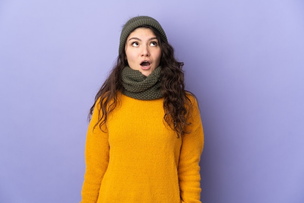 Teenager russian girl with winter hat isolated on purple wall looking up and with surprised expression
