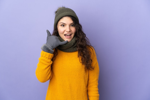 Teenager russian girl with winter hat isolated on purple wall making phone gesture. call me back sign