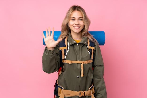 Русская альпинистка-подросток с большим рюкзаком изолирована на розовом, считая пять пальцами
