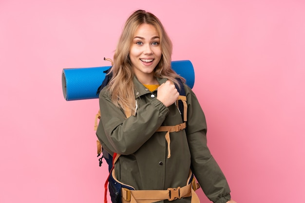 勝利を祝うピンクの壁に分離された大きなバックパックを持つ10代のロシアの登山家の女の子