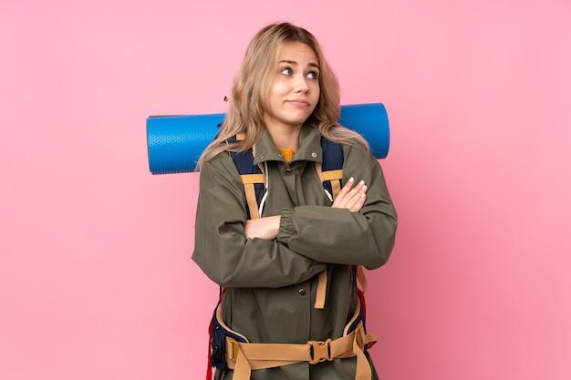 Русская альпинистка-подросток с большим рюкзаком изолирована на розовой стене, делая жест сомнения, поднимая плечи