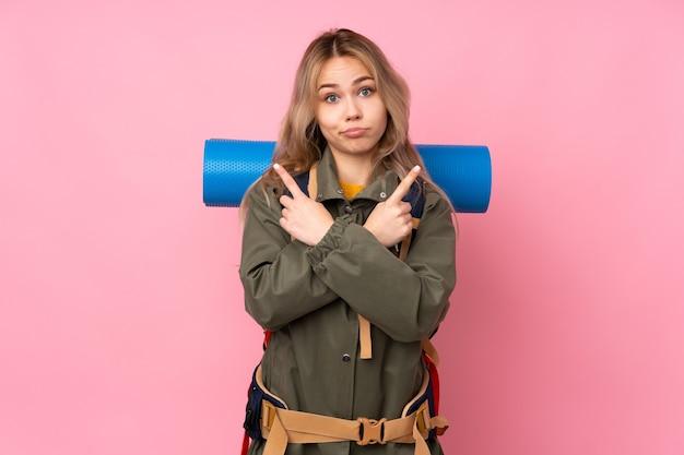 Русская альпинистка-подросток с большим рюкзаком изолирована на розовой стене, указывая на боковые стороны, имея сомнения