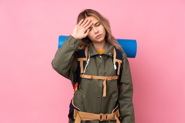 Русская альпинистка-подросток с большим рюкзаком изолирована на розовом с усталым и больным выражением лица