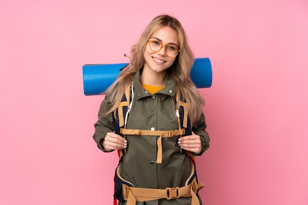 Teenager russian mountaineer girl with a big backpack isolated on pink wall with glasses and smiling