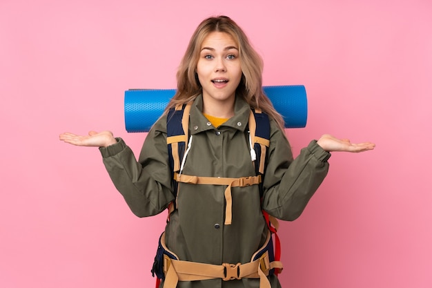 Teenager russian mountaineer girl with a big backpack isolated on pink with shocked facial expression