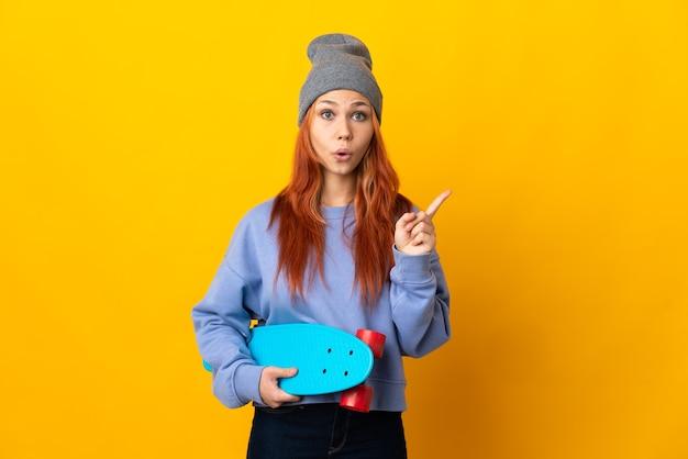 손가락을 들어 올리는 동안 솔루션을 실현하려는 노란색 배경에 고립 된 십 대 러시아 스케이팅 소녀