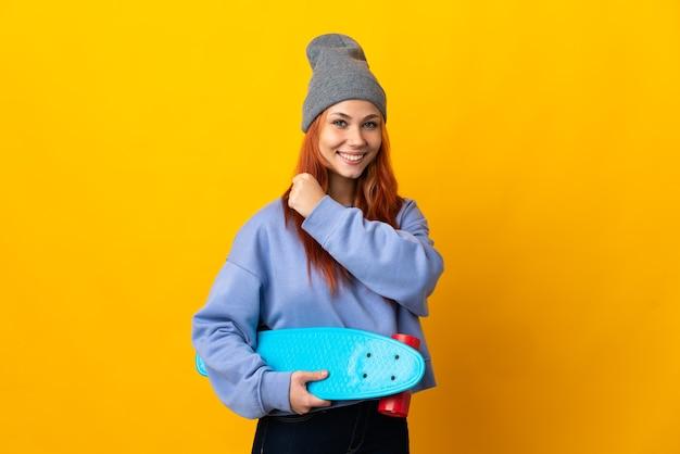Русская фигуристка-подросток, изолированная на желтой стене, празднует победу
