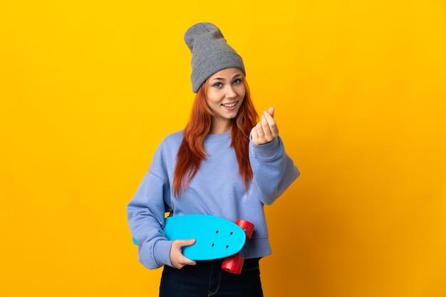 お金のジェスチャーを作る黄色の壁に分離された10代のロシアのスケーターの女の子