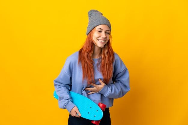 たくさん笑って黄色の壁に分離された10代のロシアのスケーターの女の子