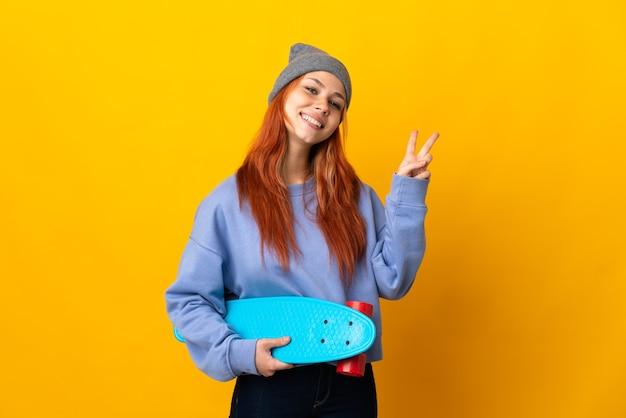 笑顔と勝利のサインを示す黄色の壁に分離された10代のロシアのスケーターの女の子