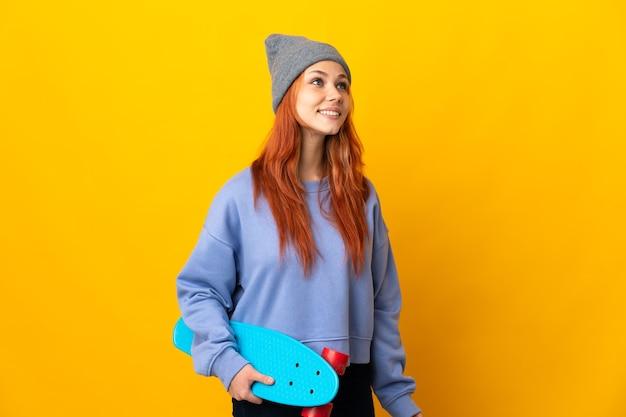 見上げながらアイデアを考えて黄色の壁に分離された10代のロシアのスケーターの女の子