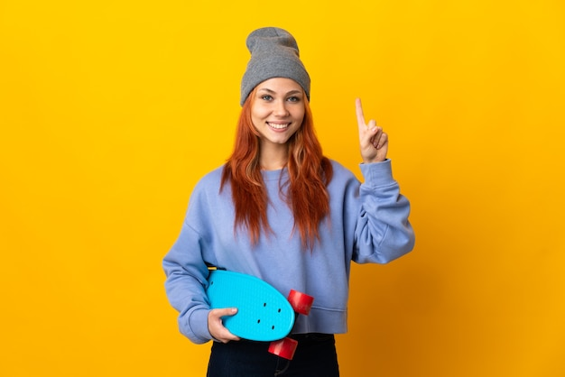 Teenager russian skater girl isolated on yellow background pointing up a great idea