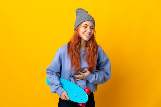 Teenager russian skater girl isolated on yellow wall smiling a lot