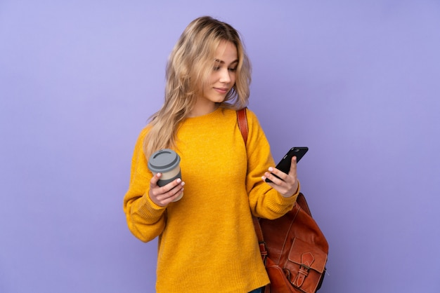 Teenager russian student girl on purple wall holding coffee to take away and a mobile