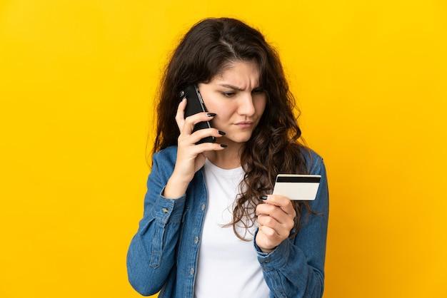 Русская женщина-подросток изолирована на желтой стене, покупая с мобильного телефона с помощью кредитной карты