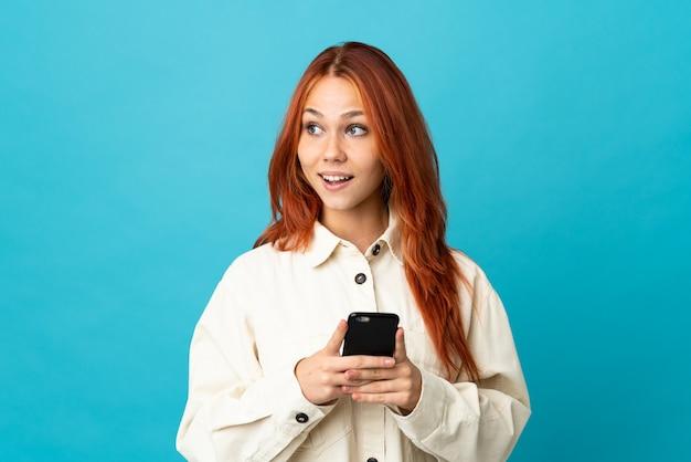10代のロシア人女性が携帯電話を使用して隔離され、見上げる