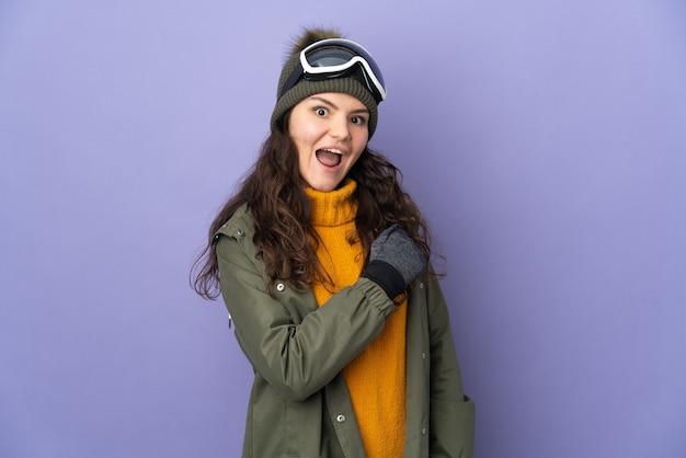 Русская женщина-подросток в очках для сноуборда изолирована на фиолетовой стене, празднуя победу