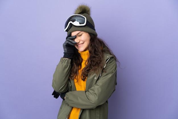 Русская женщина-подросток в очках для сноуборда изолирована на фиолетовой стене, смеясь