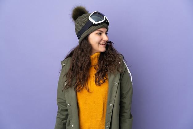 Русская женщина-подросток в очках для сноуборда изолирована на фиолетовой стене, смотрит в сторону и улыбается