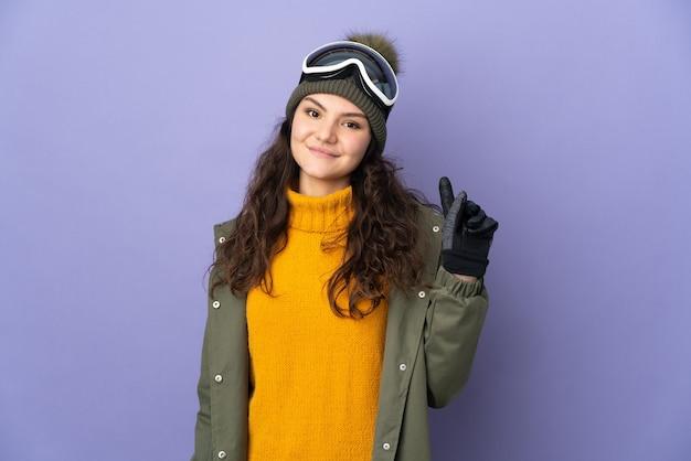 Русская женщина-подросток в очках для сноуборда изолирована на фиолетовой стене, показывая и поднимая палец в знак лучших