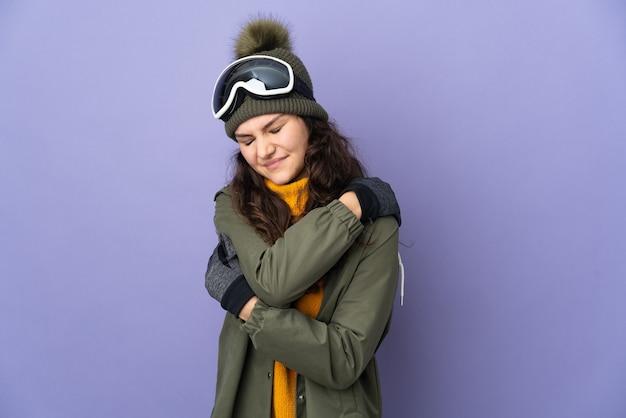 Русская женщина-подросток в очках для сноуборда изолирована на фиолетовой стене и страдает от боли в плече из-за того, что приложила усилие