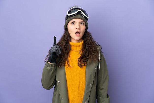 Русская женщина-подросток в очках для сноуборда изолирована на фиолетовой стене, думая об идее, указывая пальцем вверх