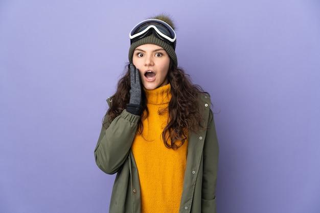 Русская женщина-подросток в очках для сноуборда изолирована на фиолетовой стене с удивленным и шокированным выражением лица