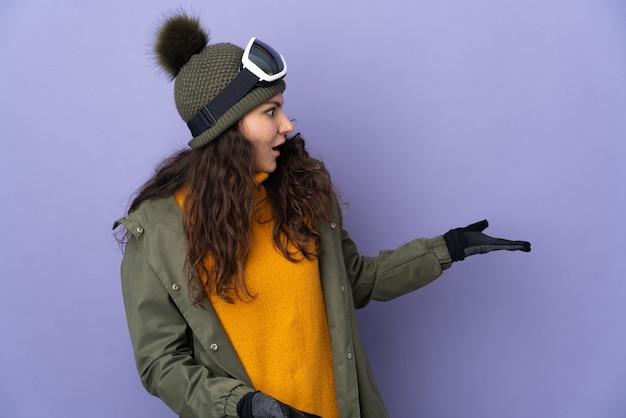 Русская женщина-подросток в очках для сноуборда изолирована на фиолетовой стене с удивленным выражением лица, глядя в сторону