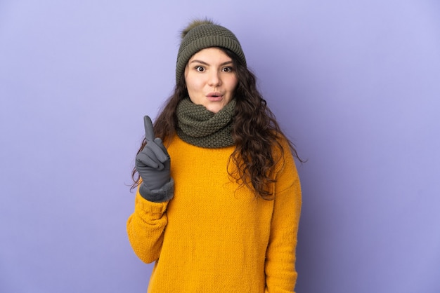 Teenager russian woman with winter hat isolated on purple wall intending to realizes the solution while lifting a finger up