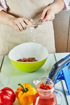 オンラインガイドを使用してサラダにティーンエイジャーの塩を入れ、自宅のキッチンで健康的な食事を準備しながらタッチタブレットでデジタルレシピを表示する