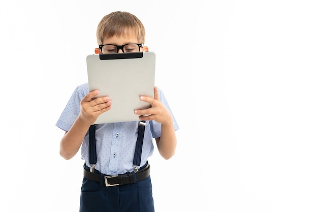Teenager school boy shows a tablet, isolated