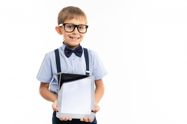 Teenager school boy shows a tablet and smiles, isolated