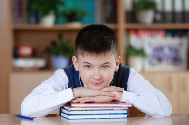 Teenager schoolboy sitting at a table with a stack of books, smiling and looking at the camera.