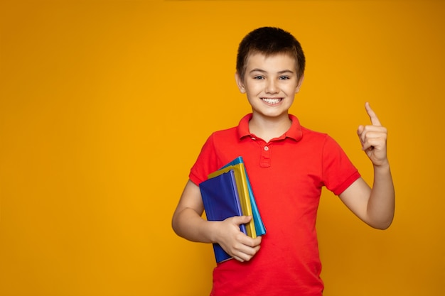 Teenager schoolboy with books on a yellow background