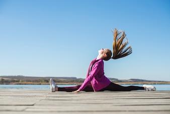 Teenager shaking hair while performing splitsr