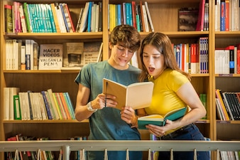 Teenager showing notebook to shocked girlfriend