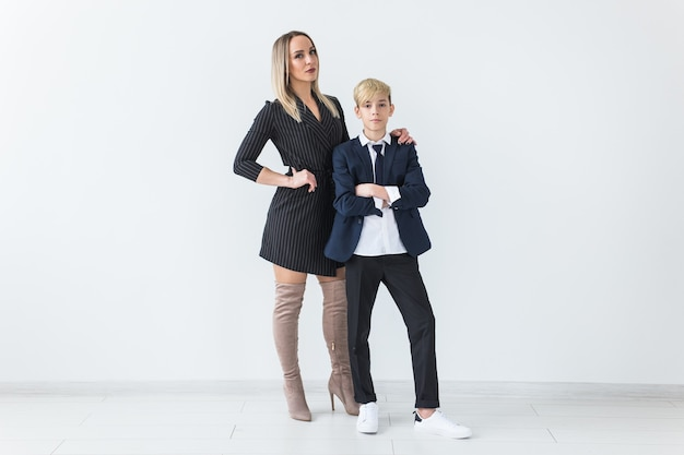 Teenager and single parent - young mother and son standing together on white background.