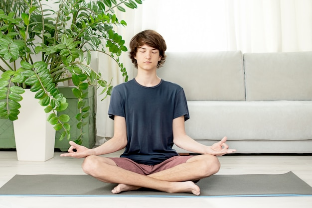 Teenager sits in lotus position on the room