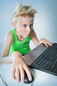 コンピューターの後ろに座っているティーンエイジャー