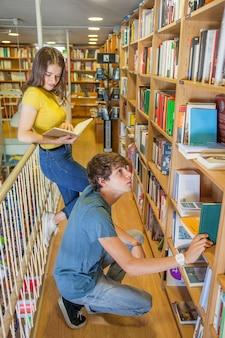 Teenager sitting on haunches and choosing book near girlfriend