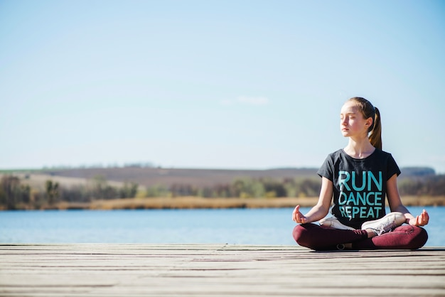 Teenager sitting on pier in lotus position