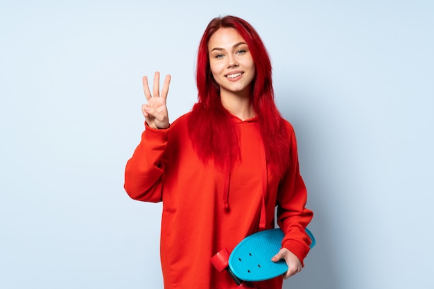 幸せと白い3本の指で数える白い壁に分離された10代のスケーターの女性