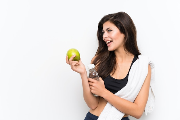 Teenager sport girl over isolated white wall with an apple and a bottle of water