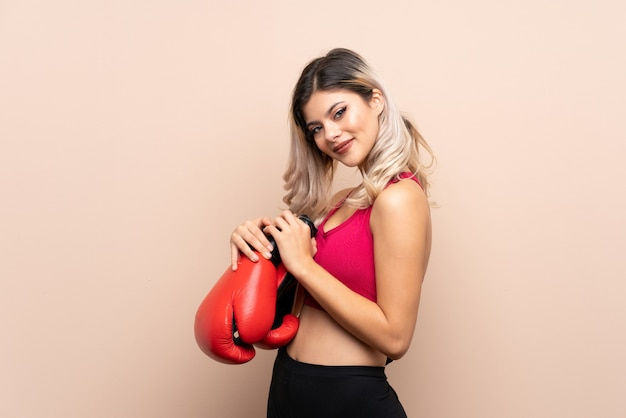 Teenager sport girl over isolated  with boxing gloves