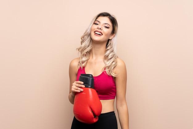 Девушка спорта подростка над изолированной предпосылкой с перчатками бокса