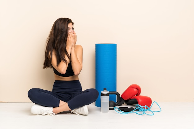 Teenager sport girl sitting on the floor covering mouth and looking to the side
