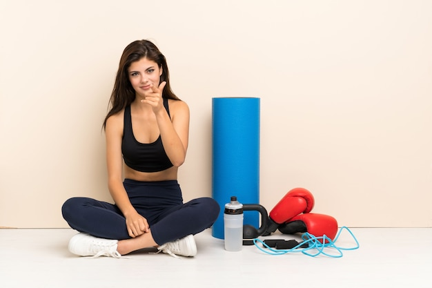 Teenager sport girl sitting on the floor frustrated and pointing to the front